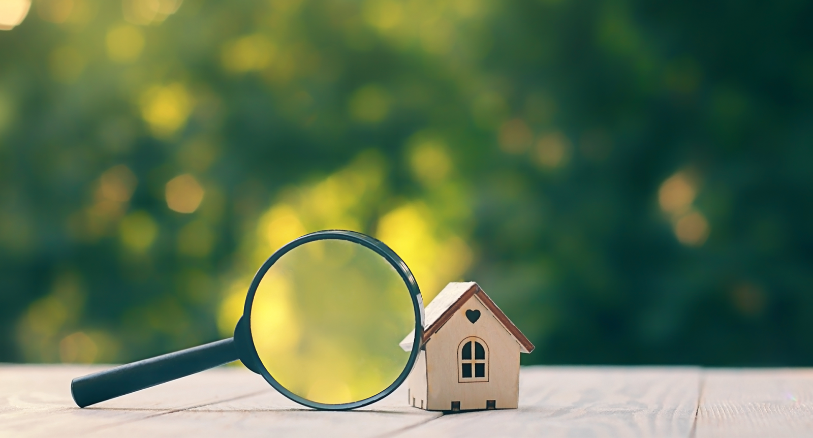 Small house on magnifying glass banner image